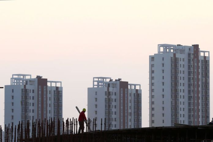 © Reuters. FILE PHOTO: Worker stands on the scaffolding at a construction site against a backdrop of residential buildings in Huaian