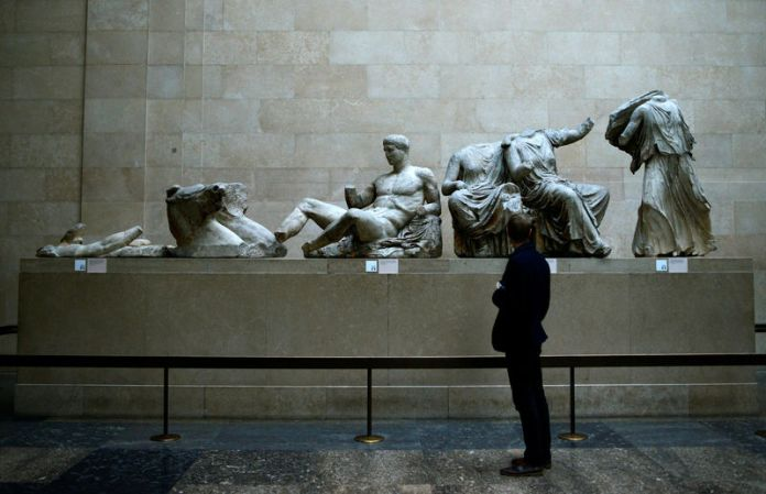 © Reuters. FILE PHOTO: A man looks at the Parthenon Marbles, a collection of stone objects, inscriptions and sculptures, also known as the Elgin Marbles, on show at the British Museum in London