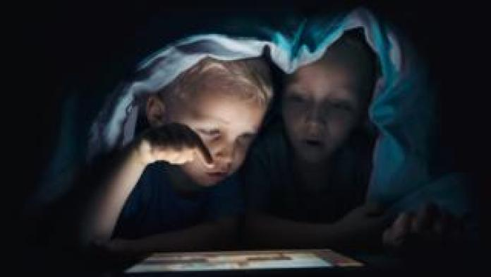 Young children looking at tablet computer under a blanket