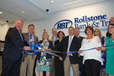 Rollstone Bank & Trust President and CEO Martin Connors Jr., left, cuts the ribbon as he and Rollstone staffers and community leaders celebrate the opening