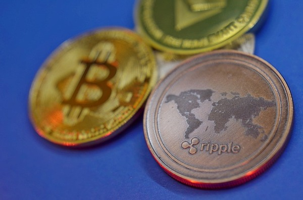 Three coins labeled bitcoin, ripple and ethereum.