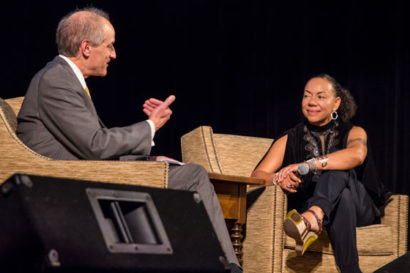 two people sit in chairs and talk on stage