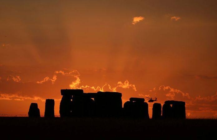 © Reuters. FILE PHOTO:  A helicopter flies behind the Stonehenge stone circle during sunset in southwest Britain