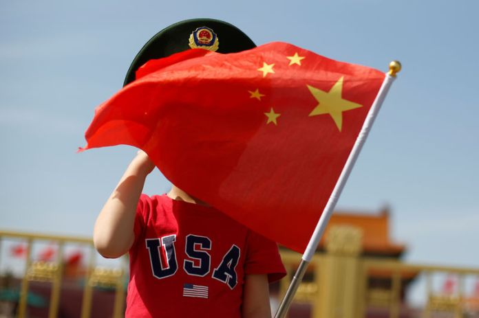 © Reuters. A boy wearing an U.S. t-shirt waves a Chinese national flag in Tiananmen Square in Beijing