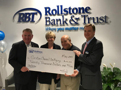 Rollstone Bank & Trust President and CEO Martin Connors Jr., left, and Rollstone COO Arthur Feehan, right, present a $20,000 check to Kathy Shelp, director