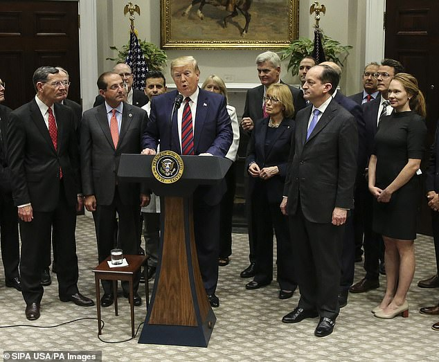 Drew Calver, 44, a high school teacher who was billed $109,000 after suffering a heart attack, was a guest President Donald Trump at the White House and called on Congress to end surprise medical bills. Pictured: Trump delivers remarks as Calver and his wife (far right) listen