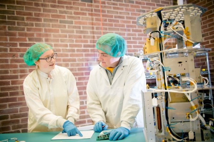 A young woman and a young man wearing scrubs, gloves, and caps in a clean room where a satellite is being assembled