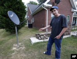 In this May 8, 2019, photo, Riley Shaw talks about his family's internet at his home outside Starkville, Miss. The satellite dish allows a certain amount of high-speed data each month and then slows to a crawl. (AP Photo/Rogelio V. Solis)