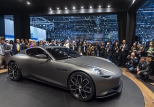 Visitors look at an electric car during the Geneva International Motor Show