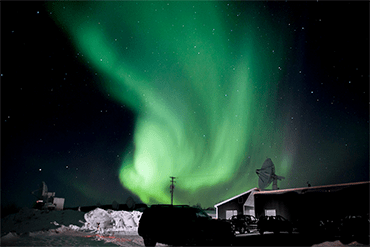 a photo of green and teal ribbons of light in the dark night sky over Alaska
