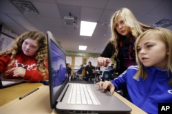 FILE: Computer science teacher Sheena York, center, helps fifth grade students work on programming during their weekly computer science lesson at Marshall Elementary School in Marysville, Wash. Photo taken Nov. 4, 2015 (AP Photo/Elaine Thompson)