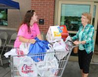 Kylee McCumber accepts a donation from Leominster resident Carol DeCarolis for Kylee's Kare Kits for Kidz outside Market Basket in Leominster on