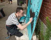 Shirley artist and Fitchburg State University graduate Ryan Normile works on a mural set to hang on the redesigned street.