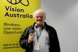 Bruce Maguire smiles in front of a Vision Australia banner.