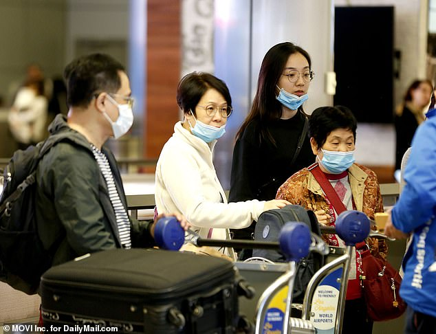 Meanwhile, an additional 63 patients across 22 states are being tested for coronavirus. Pictured: Passengers from Asia and airline staff wearing masks at Los Angeles International Airport
