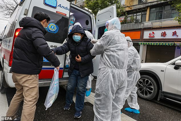 Medical staff in Wuhan, the crisis-hit city at the centre of the outbreak, help a patient off the back of an ambulance on Sunday