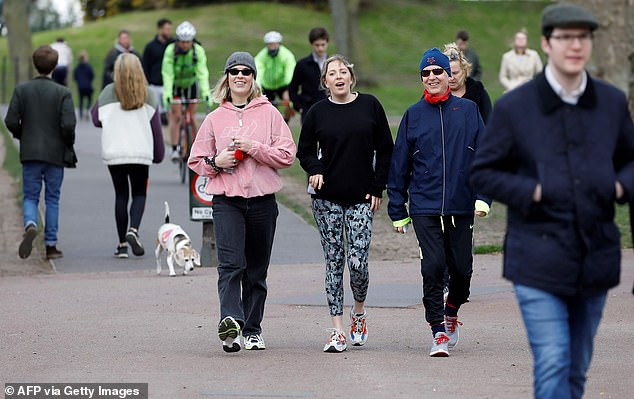 People walk to get their daily exercise allowance in Battersea Park in London today