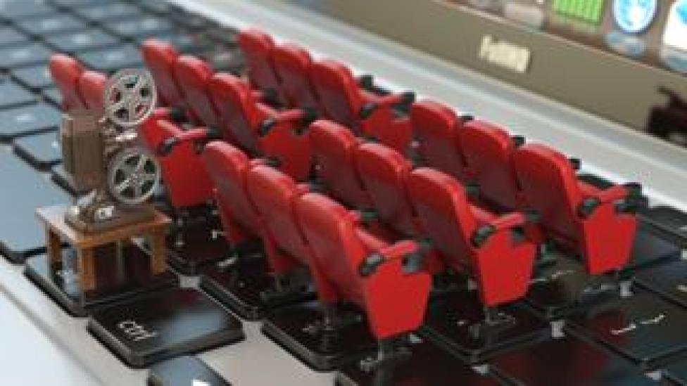 Model cinema seats are arranged in neat little rows on a laptop keyboard in this staged photo, while behind them, a model old-style film projector is perched, to illustrate the laptop screen being like a cinema