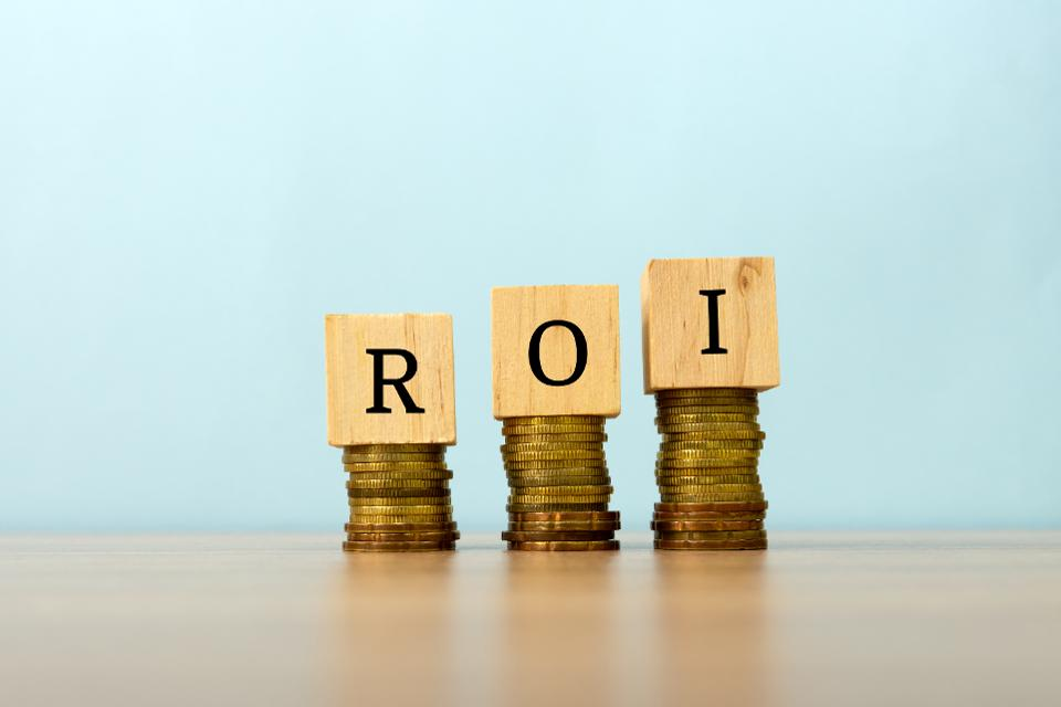 ROI text written on wooden block with stacked coins