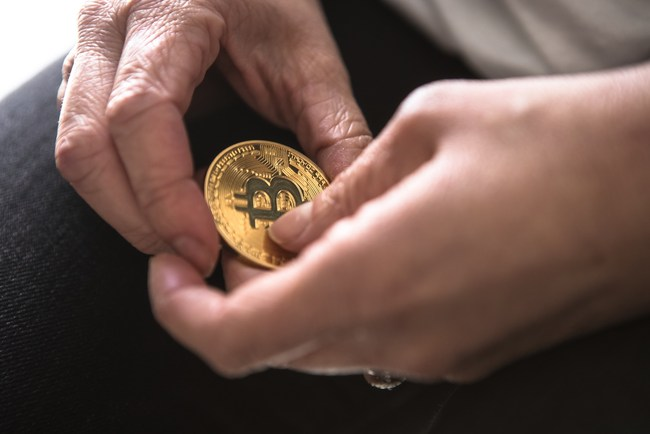 One hand passing a bitcoin on to another.