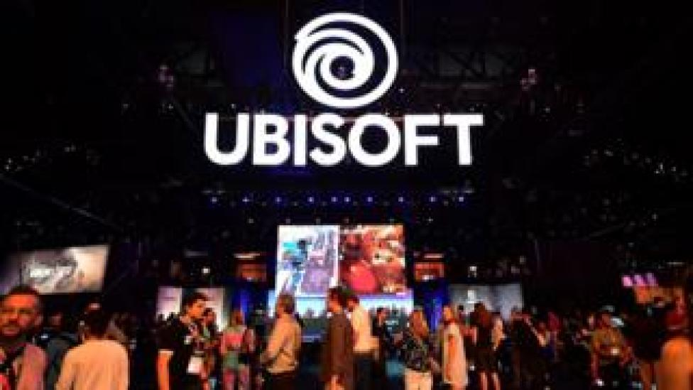 An enormous Ubisoft sign is suspended in the air at a busy trade show floor, crowded with people and displays showcasing games