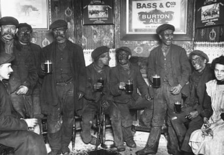 A group of coal miners, still dirty from the mines, discusses the impending national coal strike over pints of beer in February 1912.