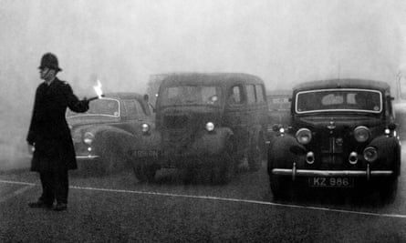 A policeman controlling traffic during the great smog in London in 1952.