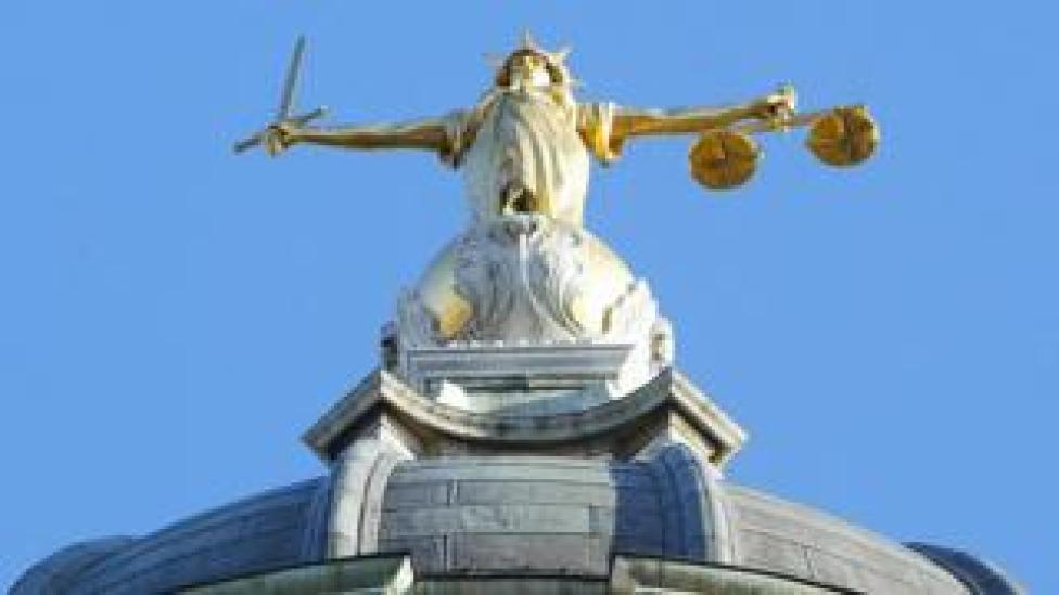 The statue of justice stands on the copula of the Old Bailey courthouse