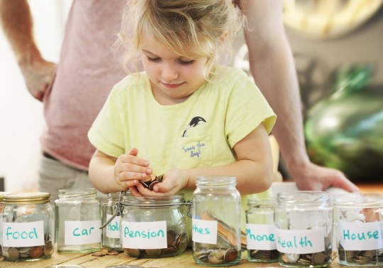 a young girl wearing a yellow t-shirt counts pennies in a jar.