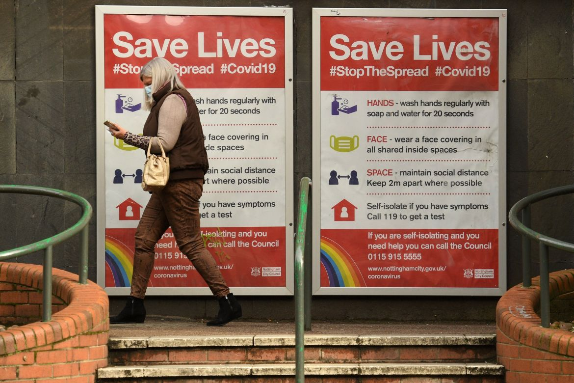 A woman wearing a mask walking past a Covid warning sign in Nottingham