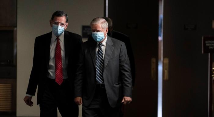 Senators John Barrasso and Lindsey Graham depart from a Republican caucus luncheon.