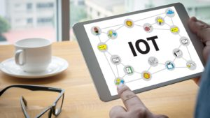 """A close-up shot of a tablet screen with """"IOT"""" text and related emoticons in a connected web."""