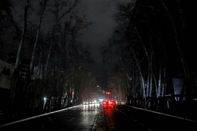 Cars drive on an unlit street during a blackout in Tehran, Iran