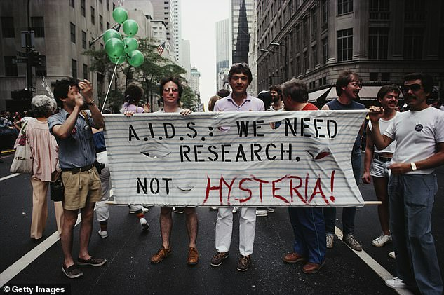Marchers on a Gay Pride parade through Manhattan, New York City, carry a banner which reads 'A.I.D.S.: We need research, not hysteria!' in June 1983