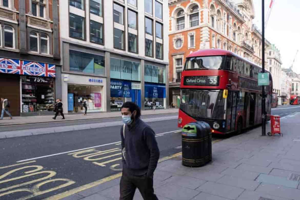 People walk through the shopping district of Oxford Street in London.