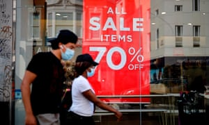 Shoppers wearing a face mask or covering due to the COVID-19 pandemic, walk past sales signs in the window of a shop in London last August