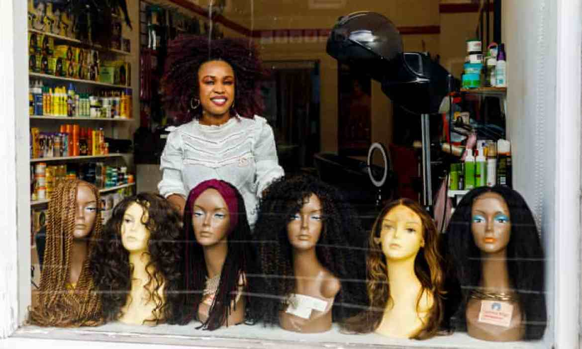 Mariam Campbell of Mayrees hair salon in Aberdeen photographed through the window with dummy heads wearing wigs in front of her