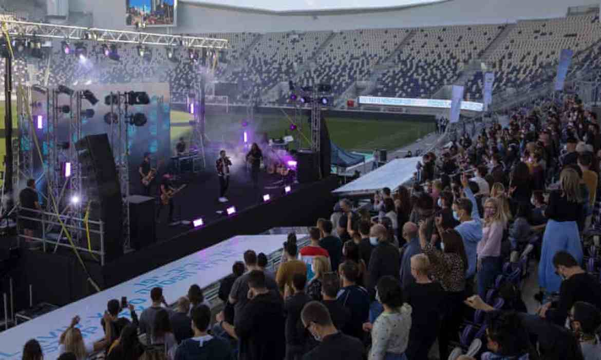 Israeli musician Ivri Lider performs in front of an audience wearing protective face masks