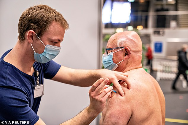 Pictured:A medical worker vaccinates a man against the coronavirus disease (COVID-19) in Frederikshavn, Jutland, Denmark, April 12, 2021 - two days before the country ceased to administer the AstraZeneca vaccine over blood clot fears
