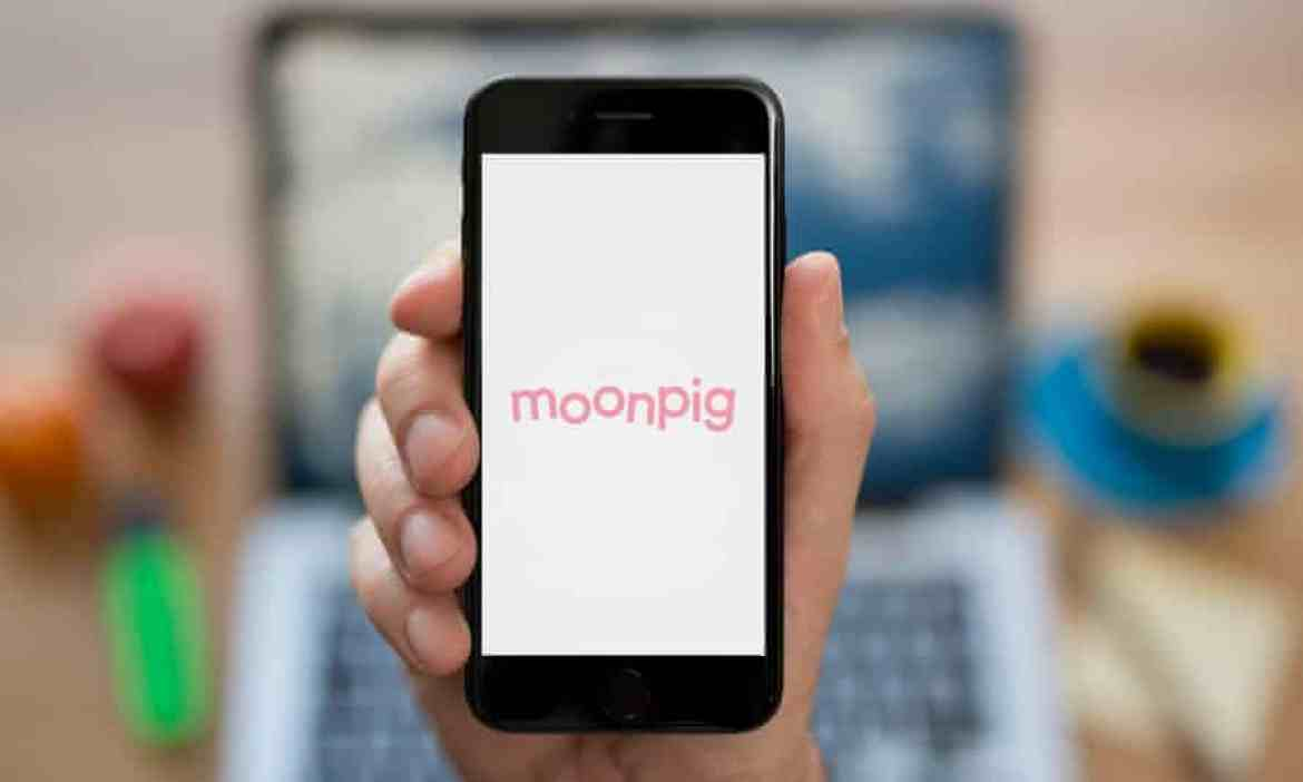 Someone holding up a phone with the pink Moonpig logo visible on the screen