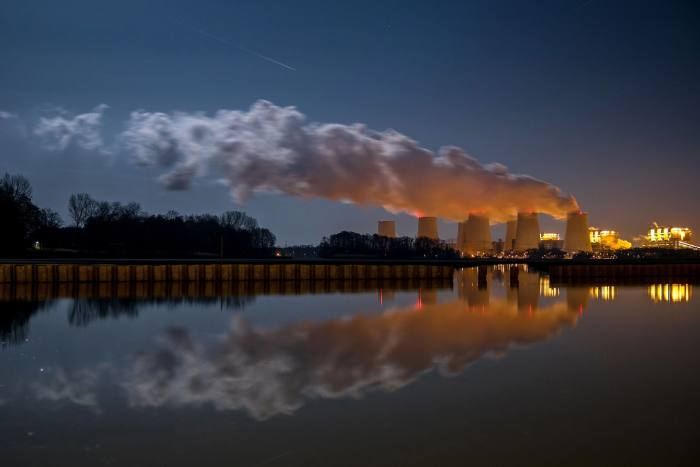 Smoke billows out of industrial chimneys, reflected in water below