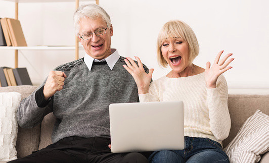 Excited senior couple celebrating victory, winning online auction bid, with a laptop on their laps.
