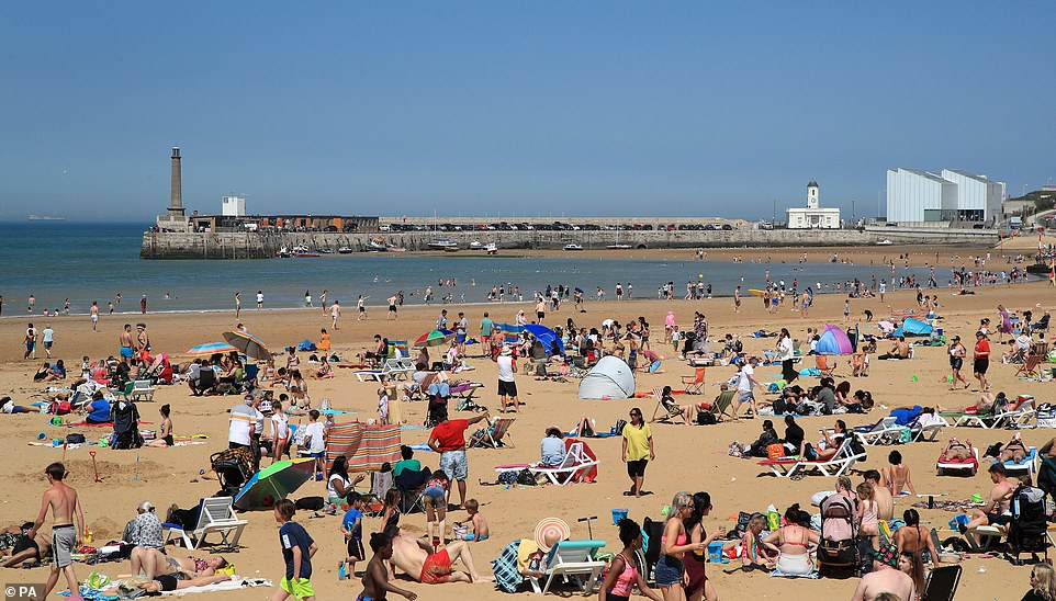 People are pictured enjoying the sunshine in Margate, Kent, today on the warmest day of the year so far with temperatures stretching towards 77F (25C) across the country