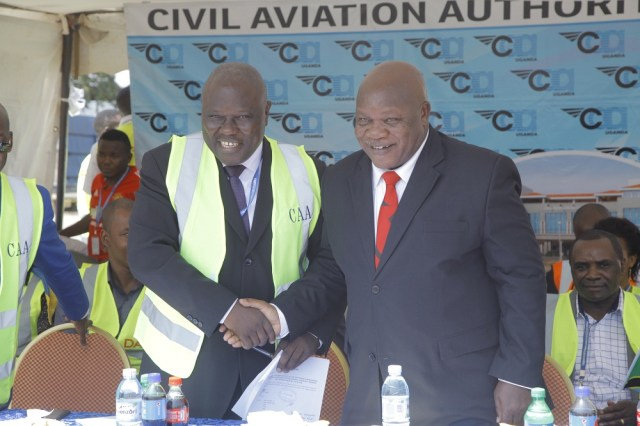 Aggrey Bagiire State Minister for Works and Transport in Uganda (L) shakes hands with Hon. Kamwelwe Isack Aloyce Minister of Transport in Tanzania (R) during the launch of Air Tanzania's inaugural flight to Uganda on August 26th 2018 at Entebbe Airport. The 76-Seater Q400 series plane touched down at 13:01pm and was received by stakeholders, Civil Aviation Authority officials and Air Tanzania officials.