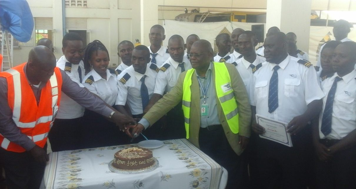 Deputy managing Director Civil Avian Authority (CAA) Fred Bamwesigye joins fire fighters and marine rescue trainees to cut the cake during their pass out at the Entebbe International Airport last Friday