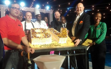 Staff of Sheraton Kampala Hotel displaying the Marriott Bonvoy launch Cake.