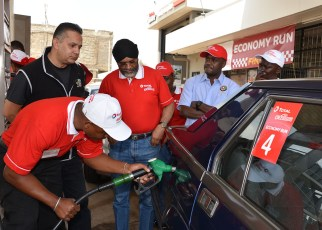 Micky Bassi (centre) watches Total Excellium Economy Run officials fill his Alfa 75 sports saloon at the finish of the 2018 event which he won. Bassi will defend his title this year on June 22nd.