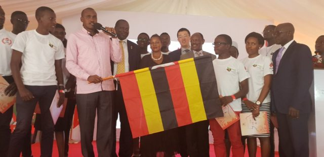 Uganda's Minister for ICT and National Guidance Frank Tumwebaze waves National Flag to flag off the 2019 Uganda Seeds for the Future Program Students to China. This was at Makerere University in Kampala.