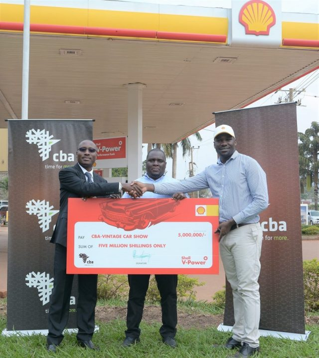 Emmanuel Ssebunya, Brand Manager- Fuels at Vivo Energy Uganda hands over a dummy cheque worth shs5 million to the CBA Uganda Vintage and Classic Auto Show organizers, Gerald Muhereza, Commercial Bank of Africa's Executive Director and John Baptist Niwagaba, the chairman Vintage Concepts.