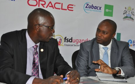 Wilbrod Owor, the Uganda Bankers Association Executive Director and the Association's Chairman Patrick Mweheire have a chat during a press briefing to announce `the 3rd Annual Bankers Conference slated for 16th July.